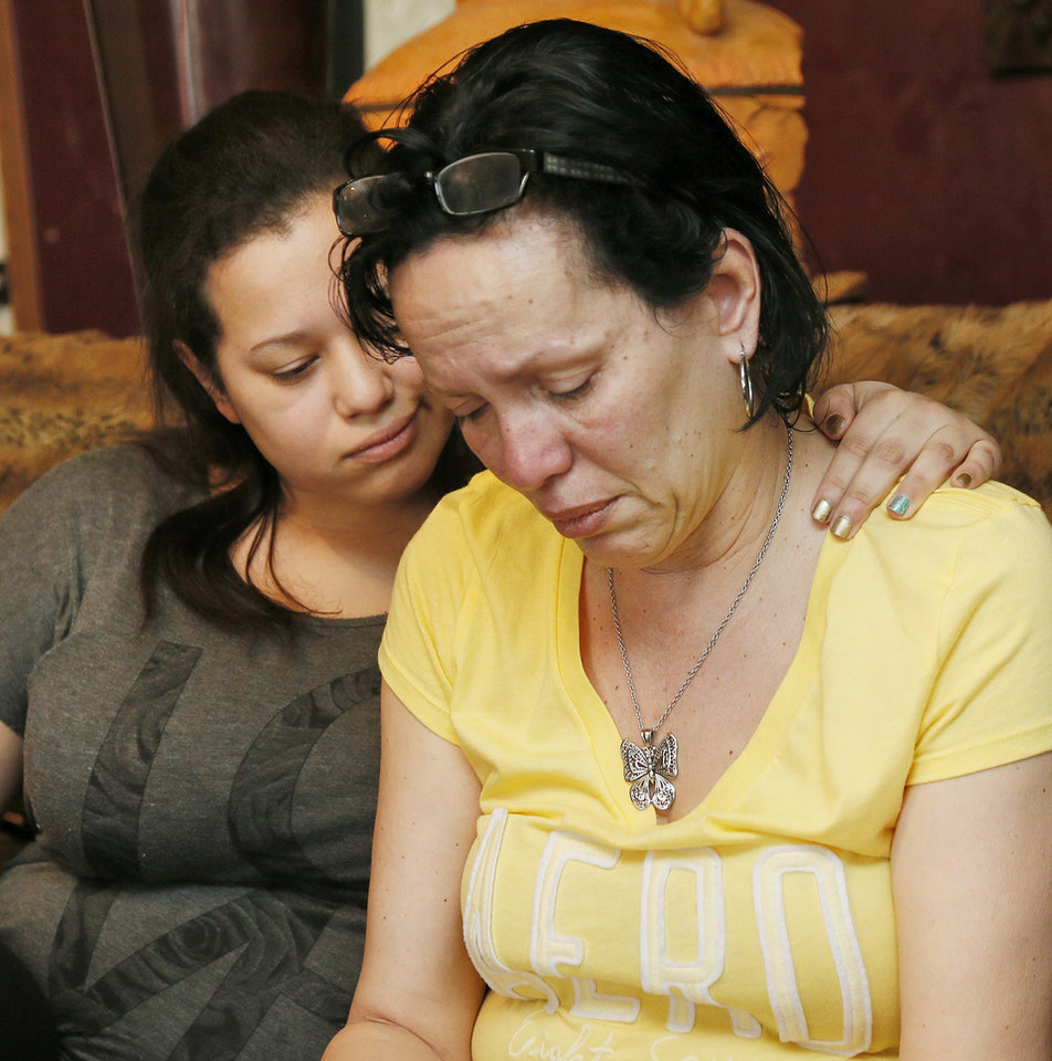 Photo - Nair Rodriguez, right, and her daughter Luinahi Rodriguez comfort each other during an interview about the death of husband and father Luis Rodriguez during an incident with Moore police at the Warren Theatre, Friday, Feb. 14, 2014. The pair are shown at the Rodriguez family's home in Norman, Okla., Monday, Feb. 17, 2014. Photo by Nate Billings, The Oklahoman