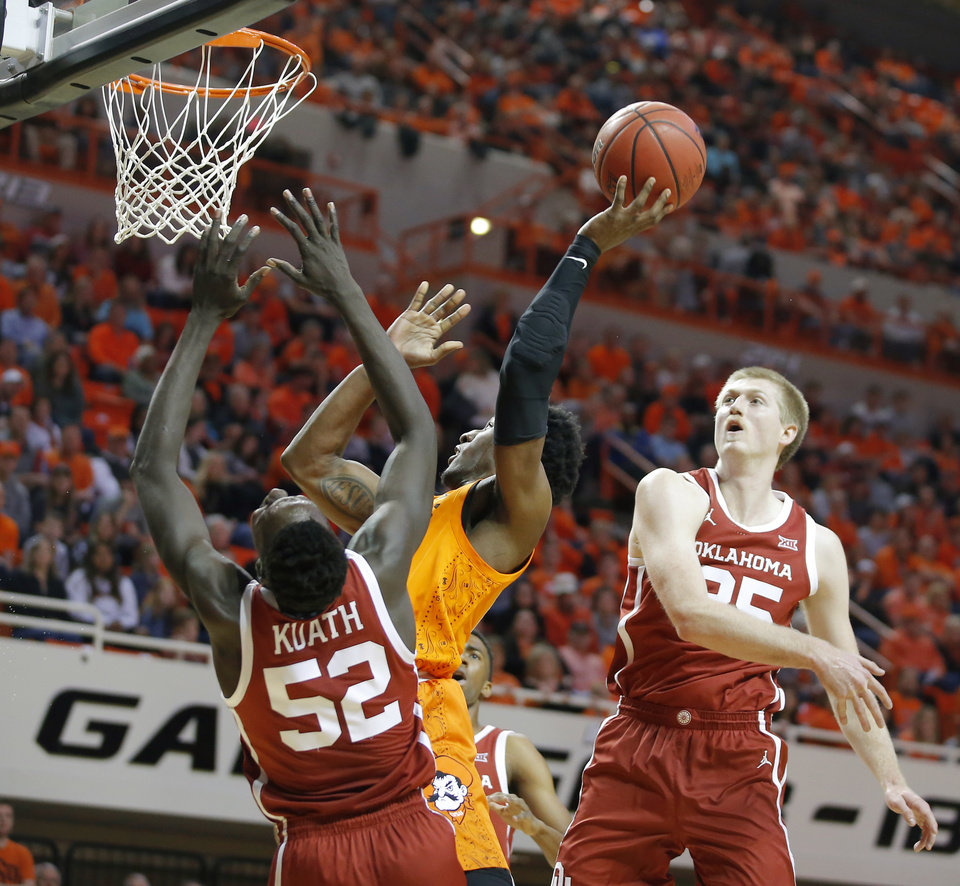 Photo - Oklahoma State's Cameron McGriff (12) makes a basket as Oklahoma's Kur Kuath (52) and Brady Manek (35) defend during an NCAA men's Bedlam basketball game between the Oklahoma State University Cowboys (OSU) and the University of Oklahoma Sooners (OU) at Gallagher-Iba Arena in Stillwater, Okla., Saturday, Feb. 22, 2020. Oklahoma State won 83-66. [Bryan Terry/The Oklahoman]
