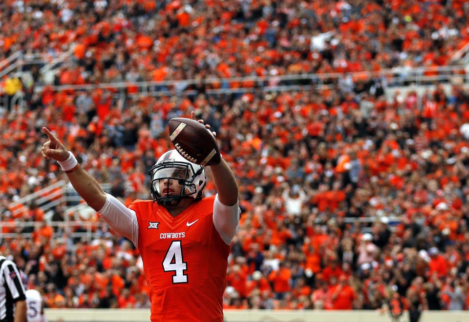 Photo - Oklahoma State's J.W. Walsh (4) celebrates a topdown in the first quarter during a college football game between the Oklahoma State University Cowboys (OSU) and the Kansas Jayhawks (KU) at Boone Pickens Stadium in Stillwater, Okla., Saturday, Oct. 24, 2015. Photo by Sarah Phipps, The Oklahoman