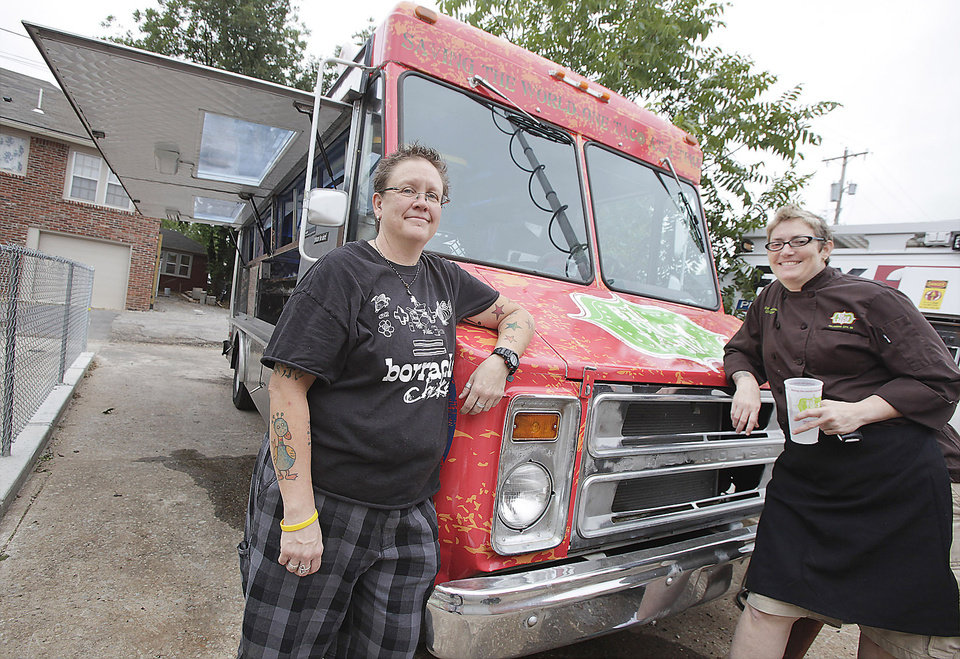 Photo - Kathryn Mathis, left, and Cally Johnson stand with one of the food vending trucks for Big Truck Tacos in Oklahoma City. Photo by Paul B. Southerland, The Oklahoman