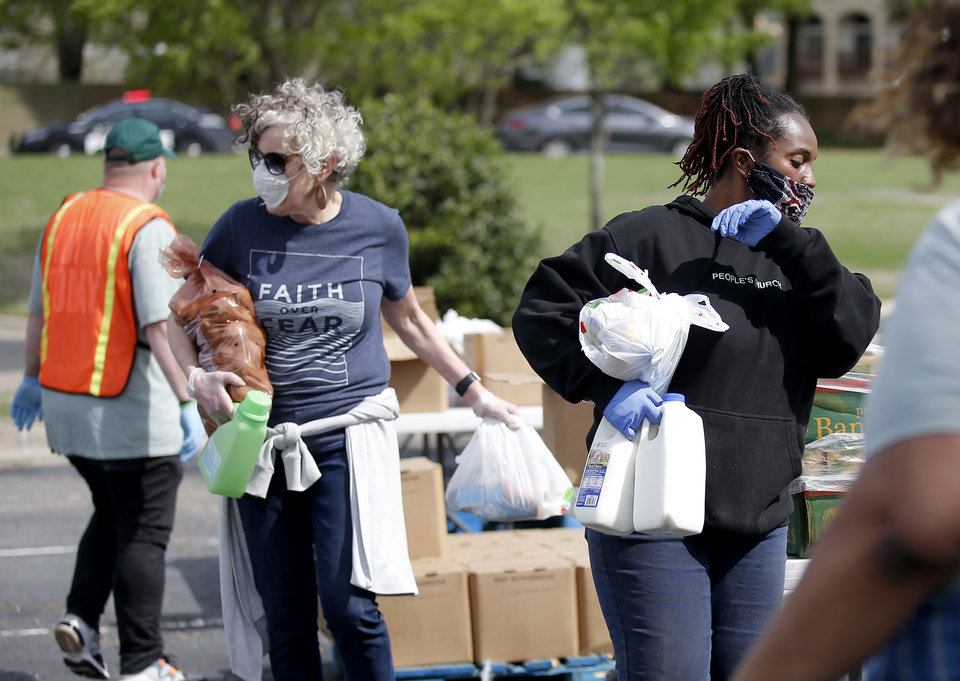 Photo - Kia Johnson, right, and Cheryl Boylow load food and supplies into cars at PeopleÕs Church, 800 E. Britton Rd., in Oklahoma City, Thursday, April 9, 2020. Cars lined up for miles for hours as the church members gave away 6,000 pounds of free groceries and supplies. [Sarah Phipps/The Oklahoman]