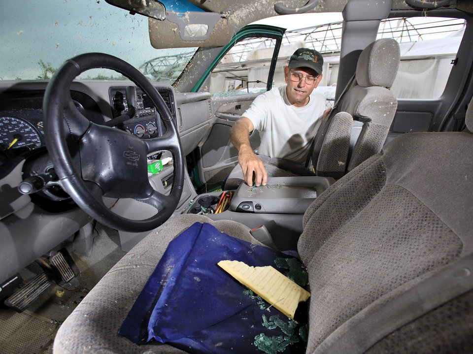Photo - Larry Jernigan, 62, of Shawnee, removes shards of glass from the center console of his 1999 Chevrolet pickup truck Tuesday afternoon, May 11, 2010. Jernigan  rode out a tornado inside the truck Monday evening in front of his cabinet shop on State Highway 99 in Seminloe. He hunkered down in the front seat as the twister moved his truck about 10 feet. Jernigan's truck had all the side and back windows blown out and the body received heavy damage. He escaped without injury.    Photo by Jim Beckel, The Oklahoman