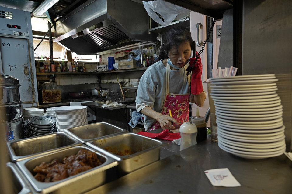 Photo -  A restaurant employee takes phone orders at a Chinese food court in Hong Kong, Wednesday, July 29, 2020. Hong Kong has banned dining-in at restaurants completely on Wednesday and make it mandatory to wear masks in all public places, as the city battles its worst coronavirus outbreak to date. (AP Photo/Vincent Yu)