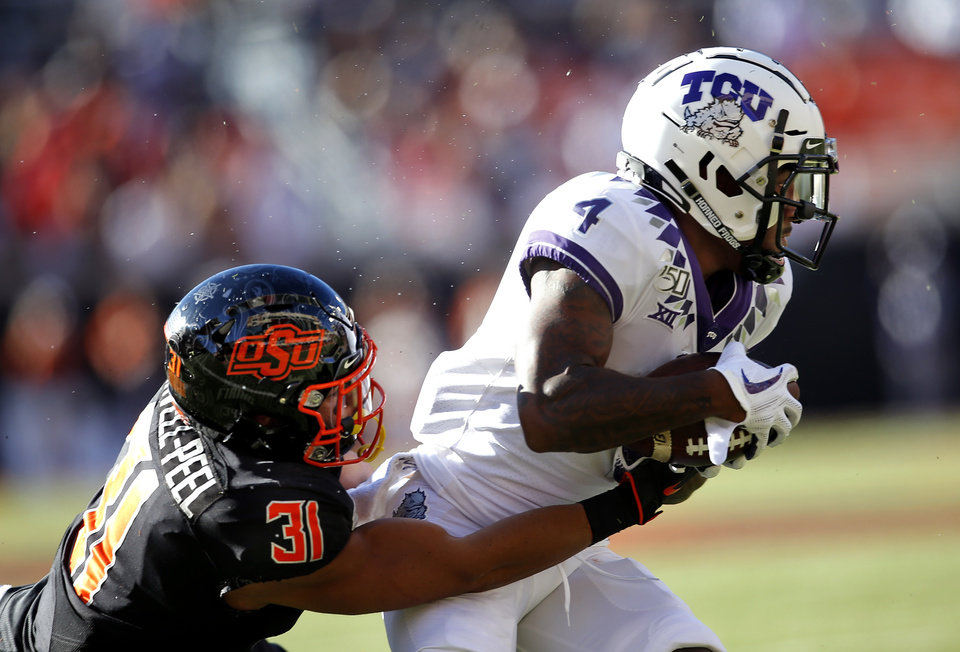Photo - Oklahoma State's Kolby Harvell-Peel (31) tackles TCU's Taye Barber (4) during the college football game between the Oklahoma State University Cowboys and the TCU Horned Frogs at Boone Pickens Stadium in Stillwater, Okla.,  Saturday, Nov. 2, 2019. OSU won 34-27. [Sarah Phipps/The Oklahoman]
