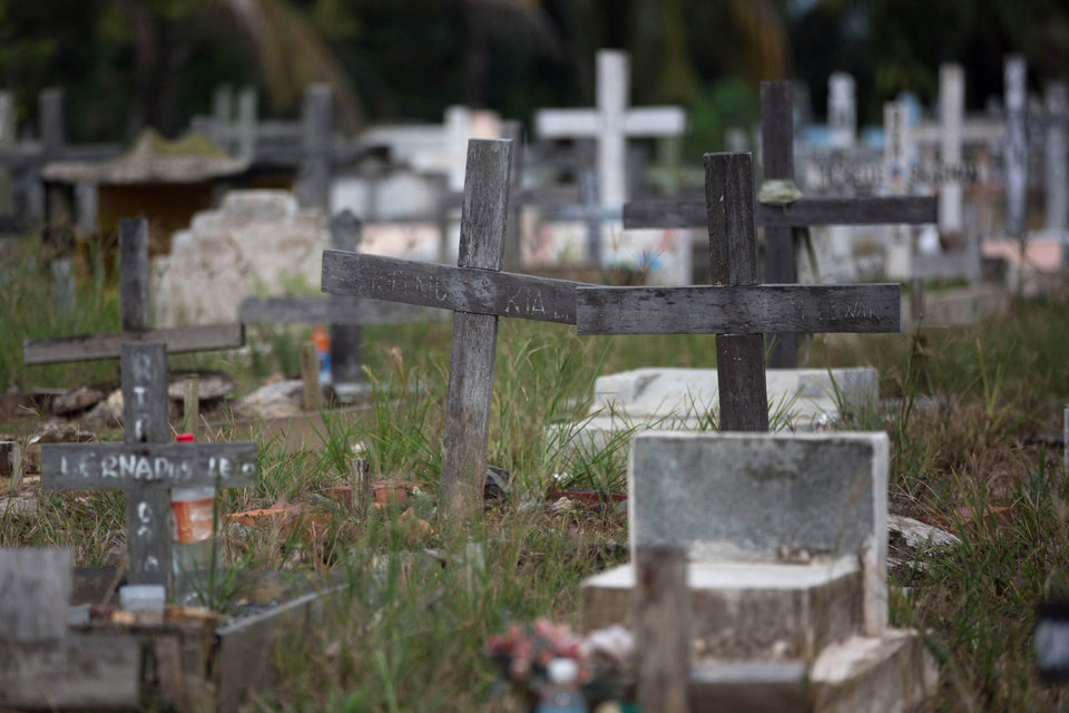 Photo -  Crosses stand in a cemetery in Tawau, Malaysia, on Sunday, Dec. 9, 2018, where the grandchild and husband of Anna, 45, a migrant worker from Indonesia, are buried. She said her son, whose newborn baby was buried next to the infant's grandfather and other migrant workers, had inherited his father's job working on a palm oil plantation. He is the family's main breadwinner. (AP Photo/Binsar Bakkara)