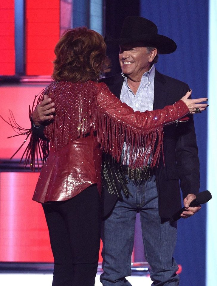Photo - Reba McEntire, left, greets George Strait as he walks onstage to present the Dick Clark artist of the decade award at the 54th annual Academy of Country Music Awards at the MGM Grand Garden Arena on Sunday, April 7, 2019, in Las Vegas. (Photo by Chris Pizzello/Invision/AP)