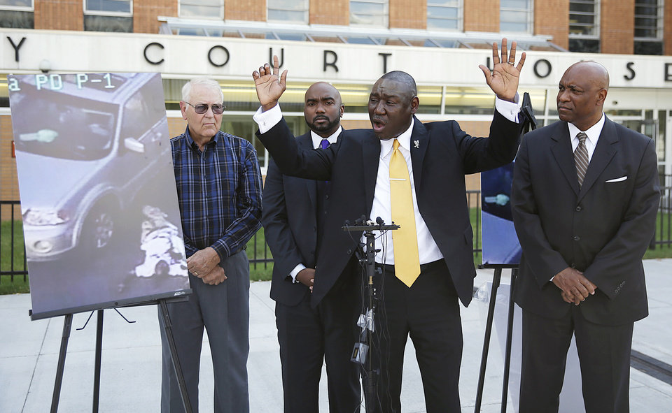 Photo - Attorney Benjamin Crump, center, one of the attorneys for Crutcher's family, says that Terence Crutcher's hands were up as he speaks during a news conference about the shooting death of Crutcher, Tuesday, Sept. 20, 2016 in Tulsa, Okla. Crutcher, was fatally shot by a Tulsa Police officer on Friday night. Also pictured are attorneys David Riggs, left, Damario Solomon-Simmons and Melvin C. Hall. (Mike Simons/Tulsa World via AP)