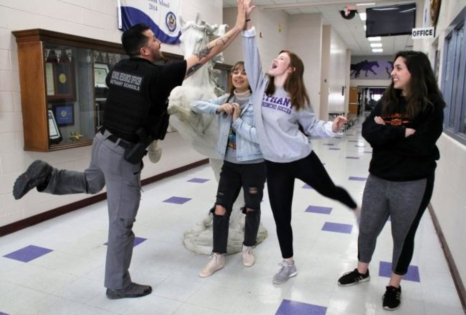 Photo -  School resource officer Zack Zamudio greets students in the hall of Bethany High School. [PHOTO PROVIDED]