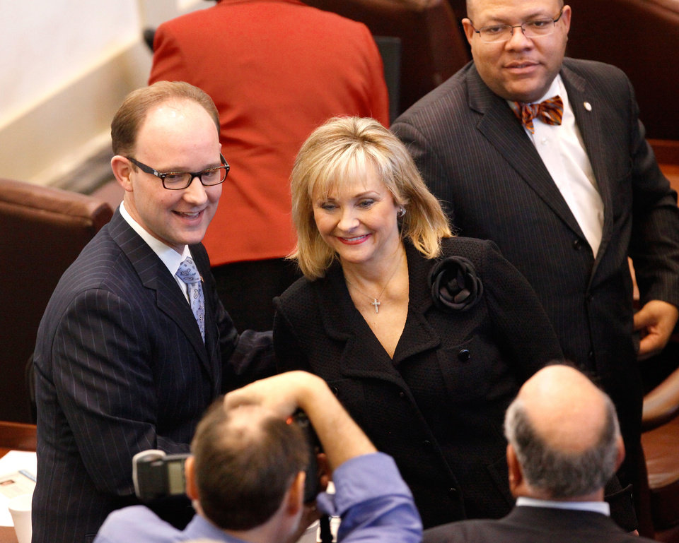 Photo - Gov. Mary Fallin stops to have her picture taken with Rep. Scot Inman as she makes her way out of the chamber after delivering her 2012 State of the State address to a joint session of the Oklahoma legislature in the House Chamber on the opening day of the session, Monday, Feb, 6, 2012.  In background is Rep. Mike Shelton.  Photo by Jim Beckel, The Oklahoman