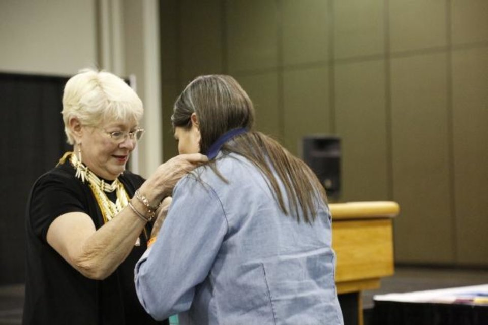 Photo -  Yonavea Hawkins, right, receives the medal for first place in beadwork from Teri Stanek, past president of the Red Earth board, at the 2019 Red Earth Festival at the Cox Convention Center in Oklahoma City, Oklahoma Friday, June 7, 2019.  [Paxson Haws/The Oklahoman]
