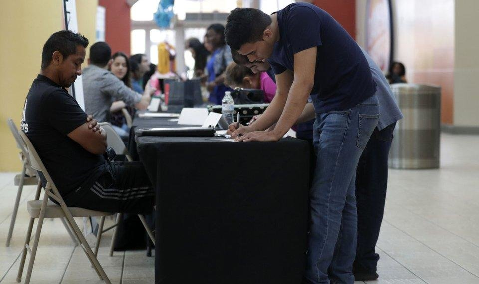 Photo - FILE - In this Oct. 1, 2019, file photo Billy Ramos, right, fills out a job application with Adidas during a job fair at Dolphin Mall in Miami. On Friday, Nov. 1, the U.S. government issues the October jobs report. (AP Photo/Lynne Sladky)