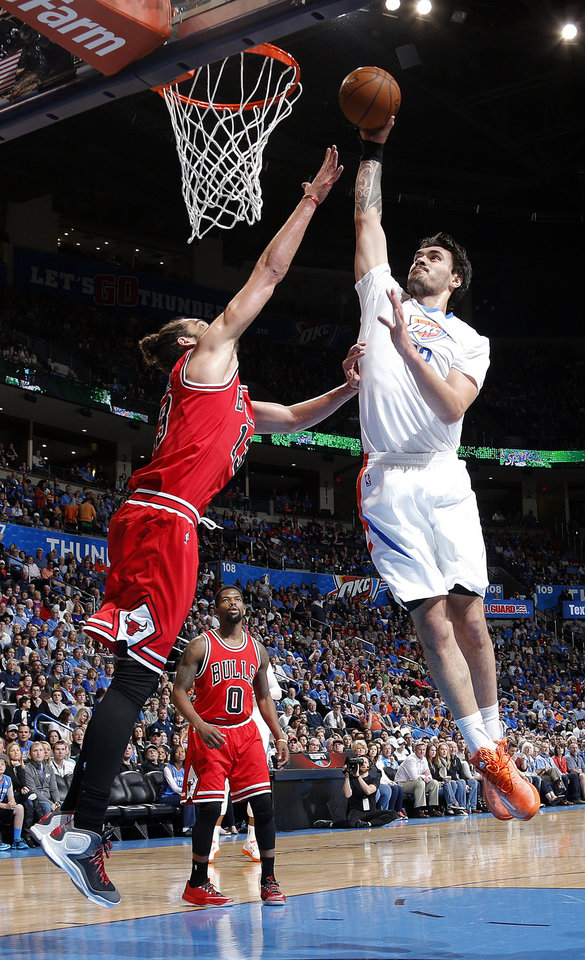 Photo - Oklahoma City's Steven Adams (12) shoots as Chicago's Joakim Noah (13) defends during the NBA game between the Oklahoma City Thunder and the Chicago Bulls at Chesapeake Energy Arena in Oklahoma City, Sunday, March  15, 2015. Photo by Sarah Phipps, The Oklahoman