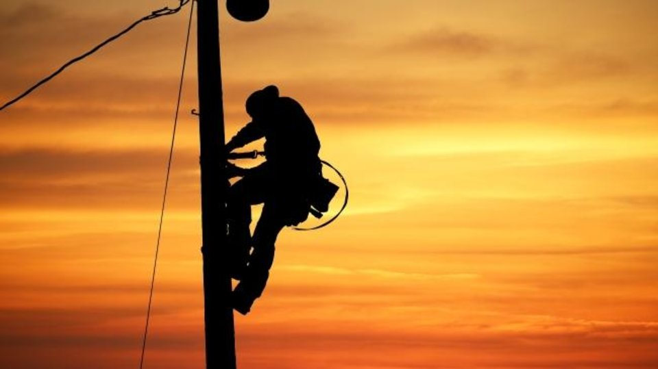 Photo -  An Oklahoma Electric Cooperative lineman climbs a pole. [PROVIDED BY OKLAHOMA ELECTRIC COOPERATIVE]