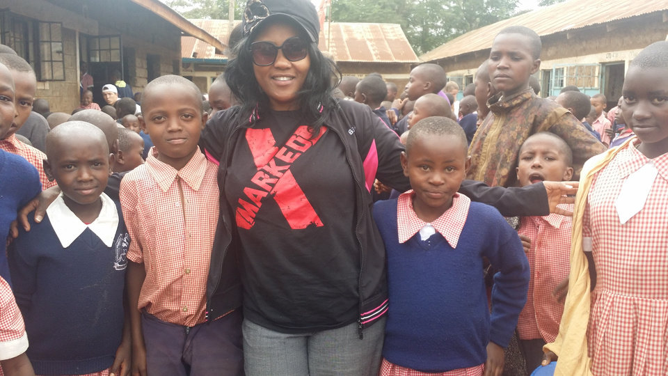 Photo -  Eunice Menja, founder of Upendo Kids International, poses with children whose education the organization sponsors. Photo provided