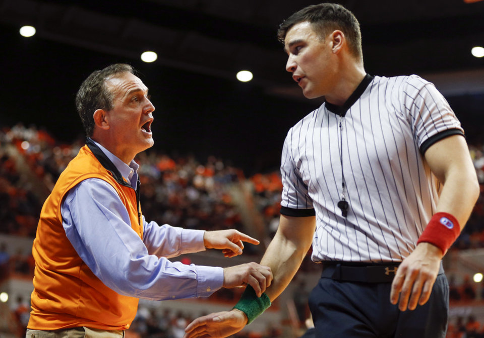 Photo - OSU coach John Smith talks to an official during a college wrestling dual between the Oklahoma State Cowboys and the Iowa Hawkeyes at Gallagher-Iba Arena in Stillwater, Okla., Sunday, Feb. 24, 2019. OSU won 27-12. Photo by Nate Billings, The Oklahoman