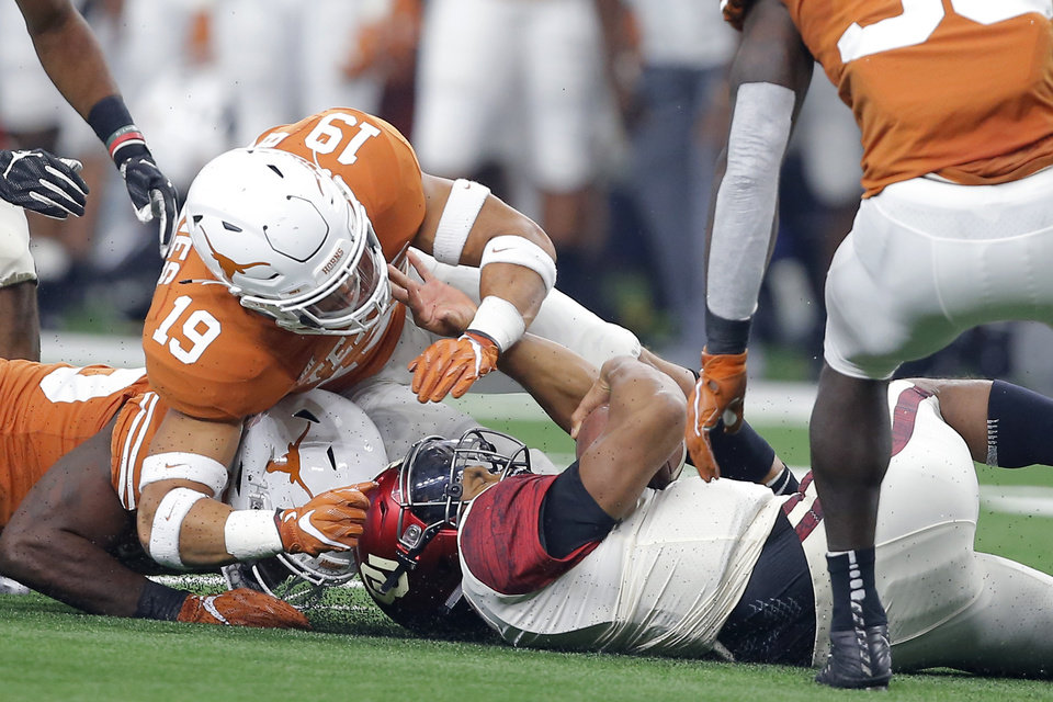 Photo - Oklahoma's Kyler Murray (1) slides down under Brandon Jones (19) of Texas during the Big 12 Championship football game between the Oklahoma Sooners (OU) and the Texas Longhorns (UT) at AT&T Stadium in Arlington, Texas, Saturday, Dec. 1, 2018.  Oklahoma won 39-27. Photo by Bryan Terry, The Oklahoman