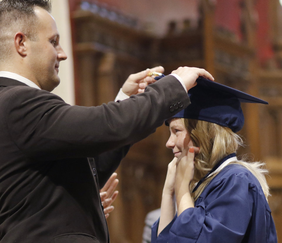 Photo - Douglas McPherson changes the tassel on Liza's cap during the Teen Recovery Solutions (TRS) at Mission Academy high school graduation ceremony at St. Paul's Episcopal Cathedral, 127 NW 7th, in Oklahoma City, Thursday, May 26, 2016. Photo by Doug Hoke, The Oklahoman