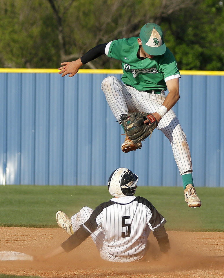 Photo - Rattan's Cal Birchfield leaps over Wright City's Justin Lecrone as the ball goes past him at second base during the Class A baseball championship game between Wright City and Rattan at Dolese Park in Oklahoma City, Saturday, May 4, 2019. [Bryan Terry/The Oklahoman]