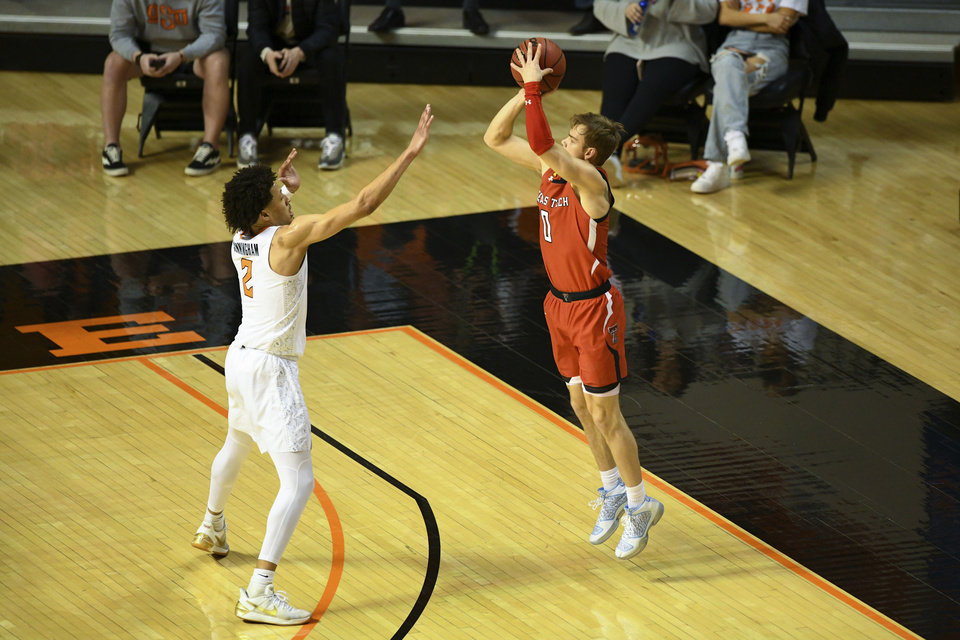 Photo - Oklahoma State guard Cade Cunningham, left, defends against a shot by Texas Tech guard Mac McClung, right,  during an NCAA college basketball game Monday, Feb. 22, 2021, in Stillwater, Okla. (AP Photo/Brody Schmidt)