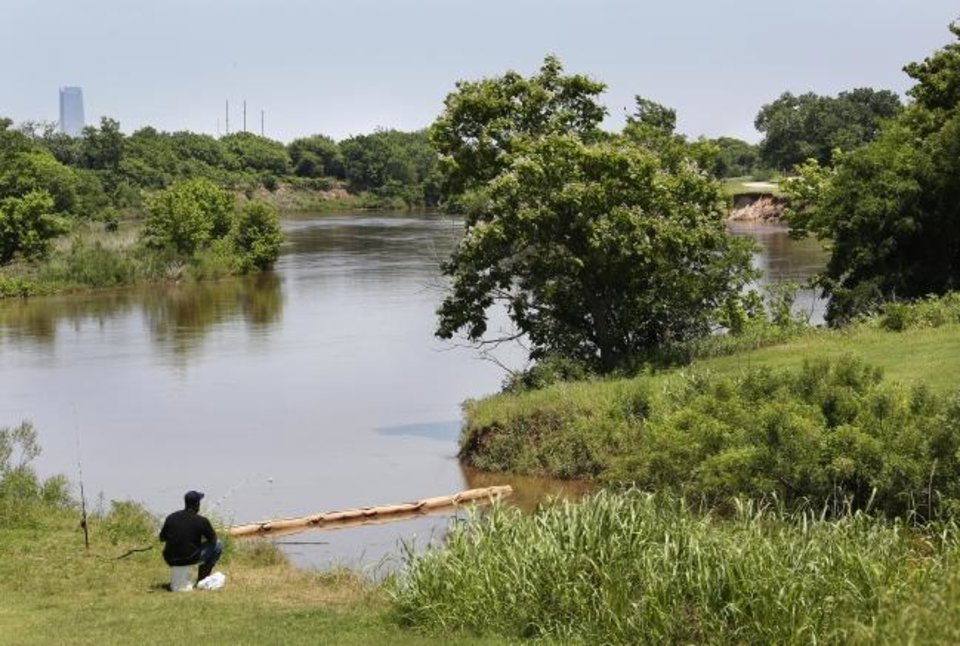 Photo -  A man fishes along the West River Trail on Thursday near the Meridian Avenue trailhead on the trail's east end.