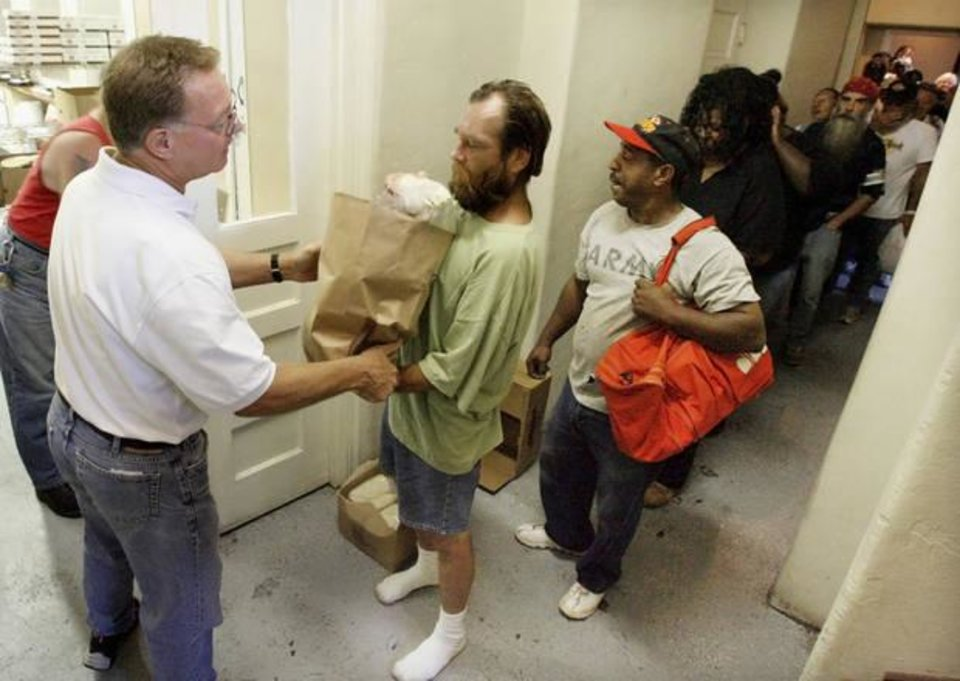 Photo - Larry Bross, director of City Care, hands a sack of groceries to a man in Oklahoma City during a grocery distribution in 2008. [Oklahoman Archives]
