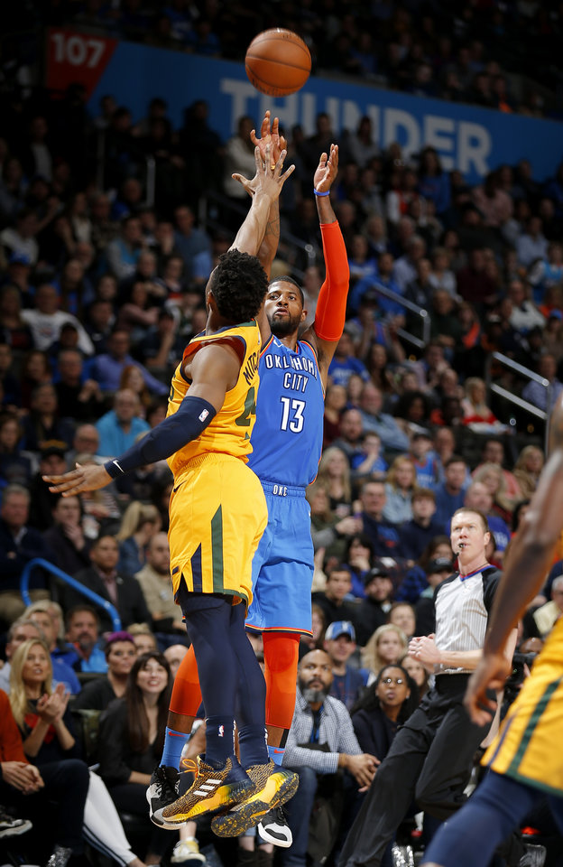 Photo - Oklahoma City's Paul George (13) shoots a 3-point basket over Utah's Donovan Mitchell (45) during the NBA game between the Oklahoma City Thunder and the Utah Jazz at the Chesapeake Energy Arena, Friday, Feb. 22, 2019. Photo by Sarah Phipps, The Oklahoman