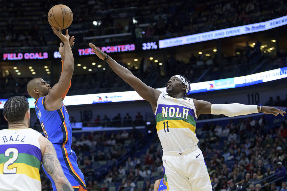 Photo - Oklahoma City Thunder guard Chris Paul (3) shoots over New Orleans Pelicans guard Jrue Holiday (11) during the first half of an NBA basketball game in New Orleans, Thursday, Feb. 13, 2020. (AP Photo/Matthew Hinton)
