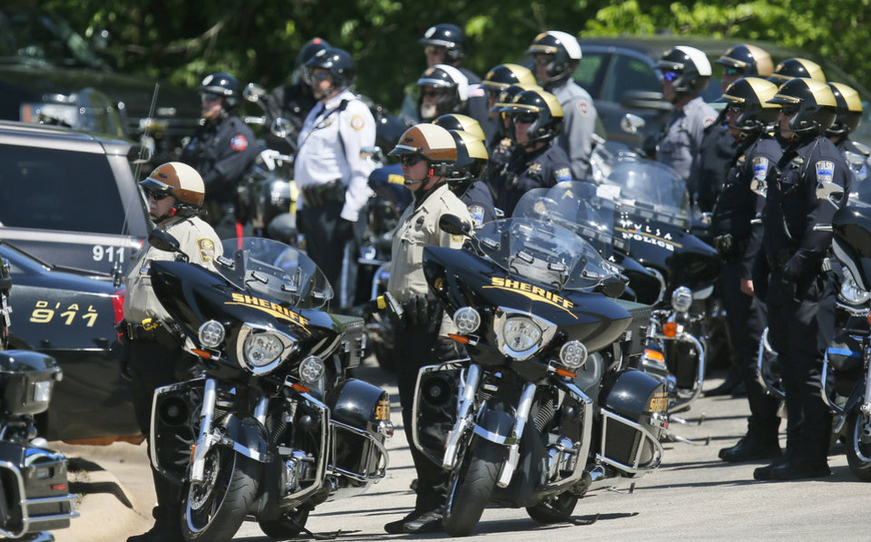 Photo - Law enforcement officers stand with their motorcycles following the funeral of Logan County Deputy David Wade in Guthrie, Okla., Monday, April 24, 2017. Wade was shot and killed while serving an eviction notice near Mulhall, Okla,. on April 18. (AP Photo/Sue Ogrocki)