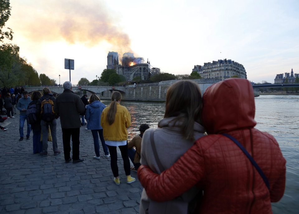 Photo - People watch as flames and smoke rise from Notre Dame cathedral as it burns in Paris, Monday, April 15, 2019. Massive plumes of yellow brown smoke is filling the air above Notre Dame Cathedral and ash is falling on tourists and others around the island that marks the center of Paris. (AP Photo/Thibault Camus)