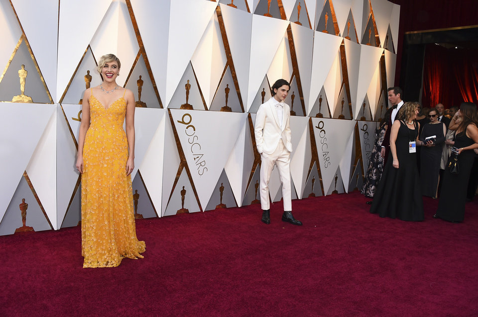 Photo - Greta Gerwig, left, and Timothee Chalamet arrive at the Oscars on Sunday, March 4, 2018, at the Dolby Theatre in Los Angeles. (Photo by Jordan Strauss/Invision/AP)