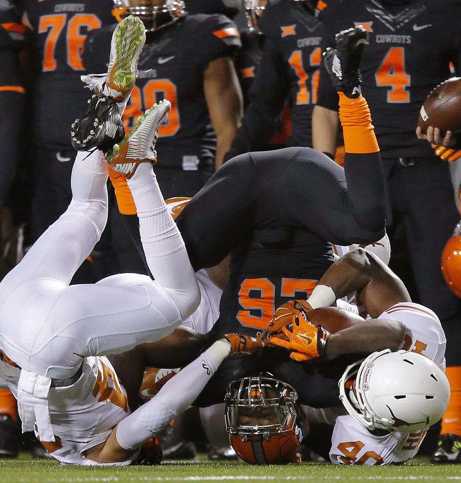 Photo - Oklahoma State's Desmond Roland (26) is upended by the Texas defense during the college football game between the Oklahoma State University Cowboys (OSU) the University of Texas Longhorns (UT) at Boone Pickens Staduim in Stillwater, Okla. on Saturday, Nov. 15, 2014.  Photo by Chris Landsberger, The Oklahoman