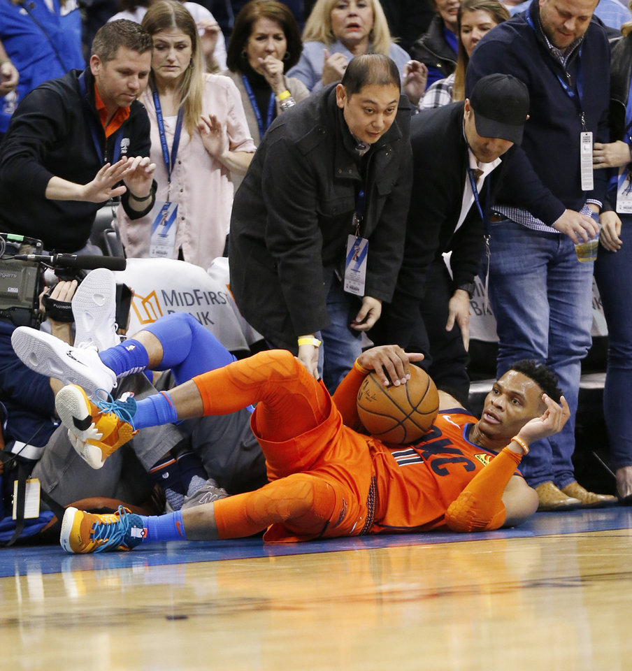 Photo - Oklahoma City's Russell Westbrook (0) looks up after being called for a foul when he collided with Dallas' Jalen Brunson (13) as they chased the ball in the fourth quarter of an NBA basketball game between the Dallas Mavericks and the Oklahoma City Thunder at Chesapeake Energy Arena in Oklahoma City, Sunday, March 31, 2019. Dallas won 106-103. Photo by Nate Billings, The Oklahoman