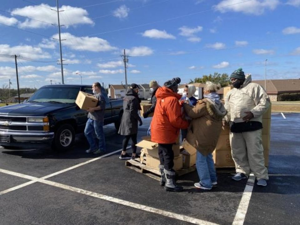 Photo -  Volunteers and leaders at Ebenezer Baptist Church take food boxes to a resident's vehicle during a drive-thru food distribution at the church, 3600 N Kelley, in partnership with World Vision. [Carla Hinton/The Oklahoman]