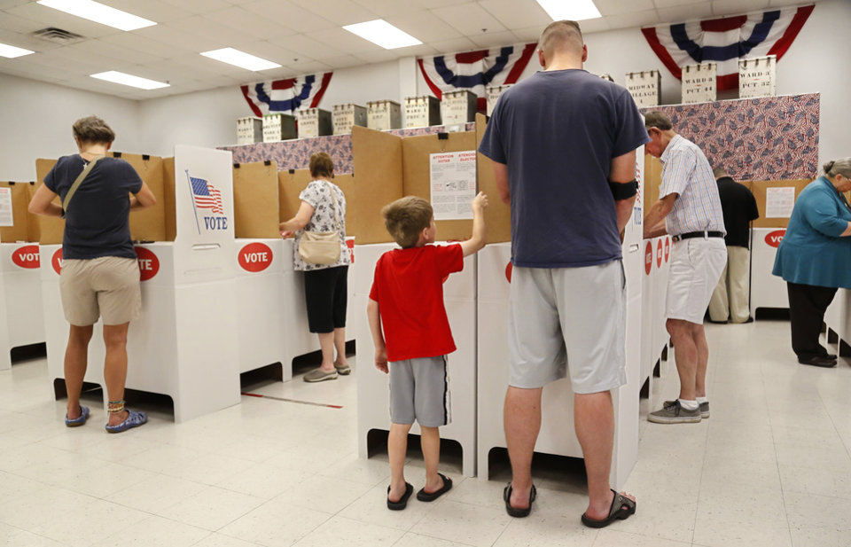 Photo -  Kayson May, 7, waits beside his father, Randy May, of Midwest City, as the elder May votes. May said he voted early because he had the day off and he wanted to be sure to vote in this election. [Photo by Jim Beckel, The Oklahoman]