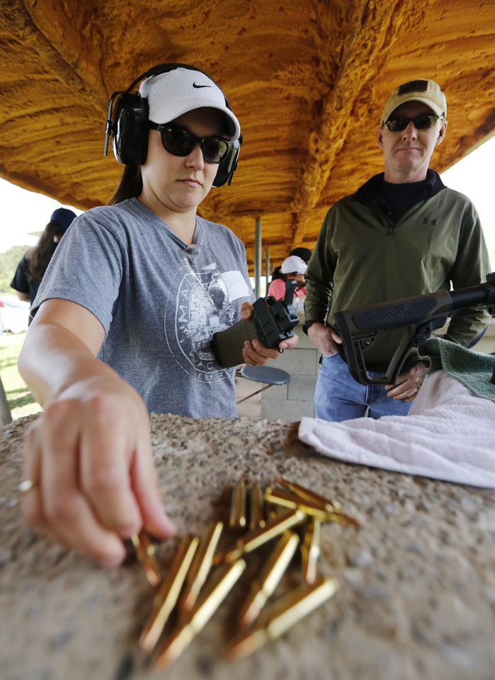 Photo -  Instructor Clay Hoover watches Laura Hensley load an AR-15 magazine. (Photo by Paul Hellstern, The Oklahoman)