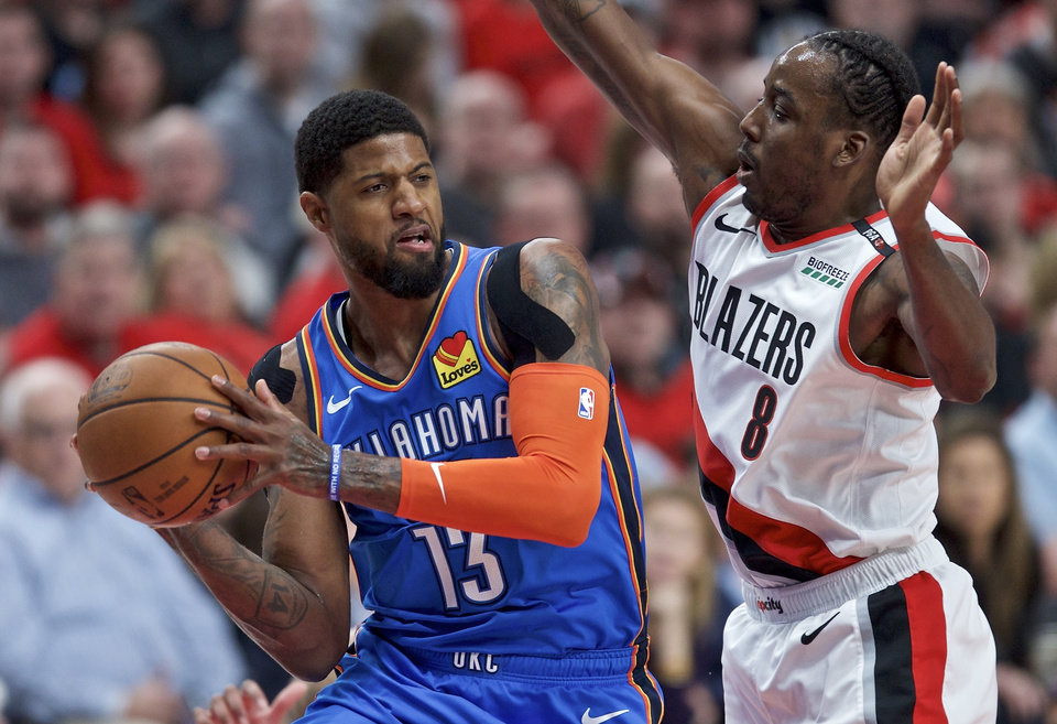 Photo - Oklahoma City Thunder forward Paul George, left, looks to pass the ball around Portland Trail Blazers forward Al-Farouq Aminu during the first half of Game 2 of an NBA basketball first-round playoff series Tuesday, April 16, 2019, in Portland, Ore. (AP Photo/Craig Mitchelldyer)