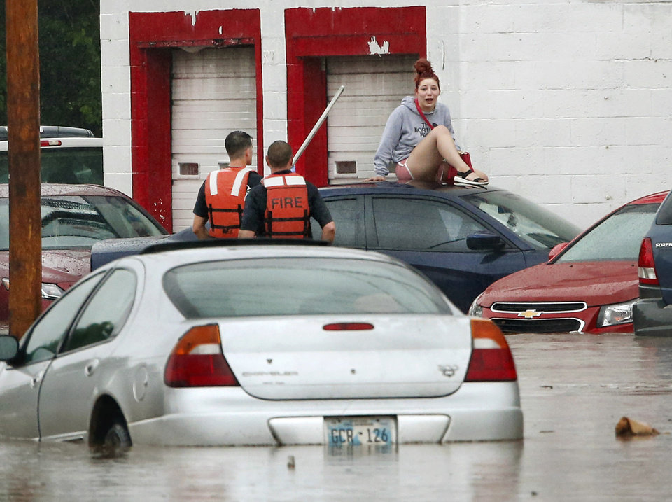 Photo - Oklahoma City firefighters rescue a woman who climbed to the roof of her car as waters on S. May Avenue rose during heavy rain Thursday morning, June 6, 2019.  Firefighters said they assisted four people to safety between 11 o'clock and noon in the deep water that flooded the intersection of SW 29 and May after heavy rains overwhelmed stormwater drainage systems and caused flooded streets, requiring  high water rescues in Oklahoma City as another round of severe storms passes through the metro.[Jim Beckel/The Oklahoman]