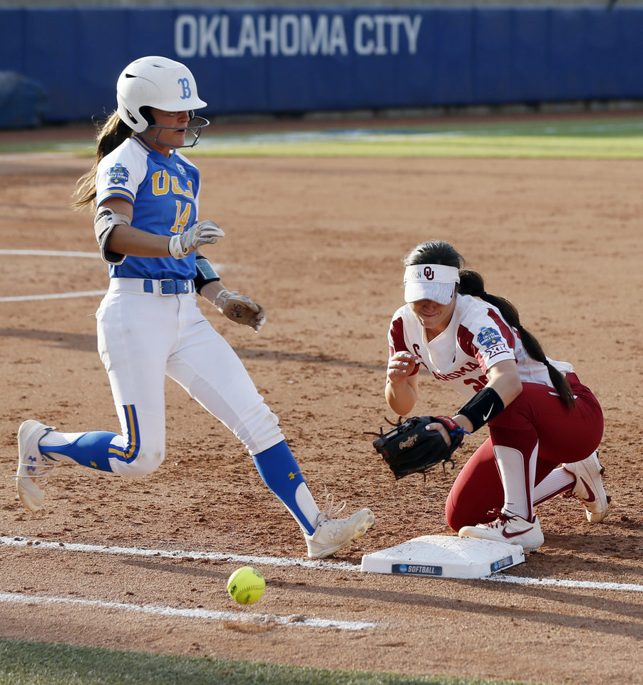 Photo - The throw gets past OU's Caleigh Clifton (20) as UCLA's Kelli Godin (14) makes it to first base before advancing to second in the third inning during the first NCAA softball game in the championship series of the Women's College World Series between Oklahoma and UCLA at USA Softball Hall of Fame Stadium in Oklahoma City, Monday, June 3, 2019. [Nate Billings/The Oklahoman]