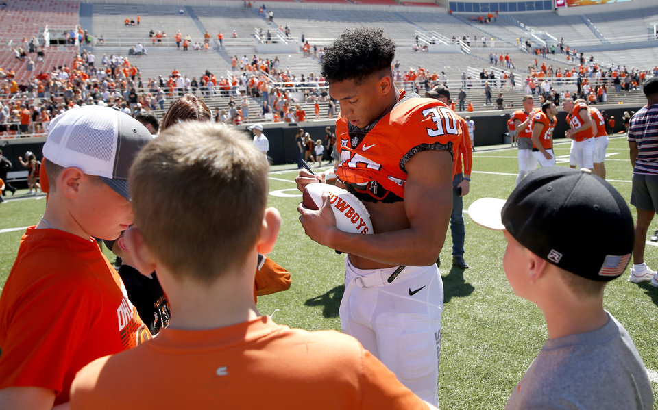 Photo - Oklahoma State's Chuba Hubbard (30) signs autographs for fans following the Oklahoma State Cowboys spring practice at Boone Pickens Stadium in Stillwater, Okla., Saturday, April 20, 2019.  Photo by Sarah Phipps, The Oklahoman