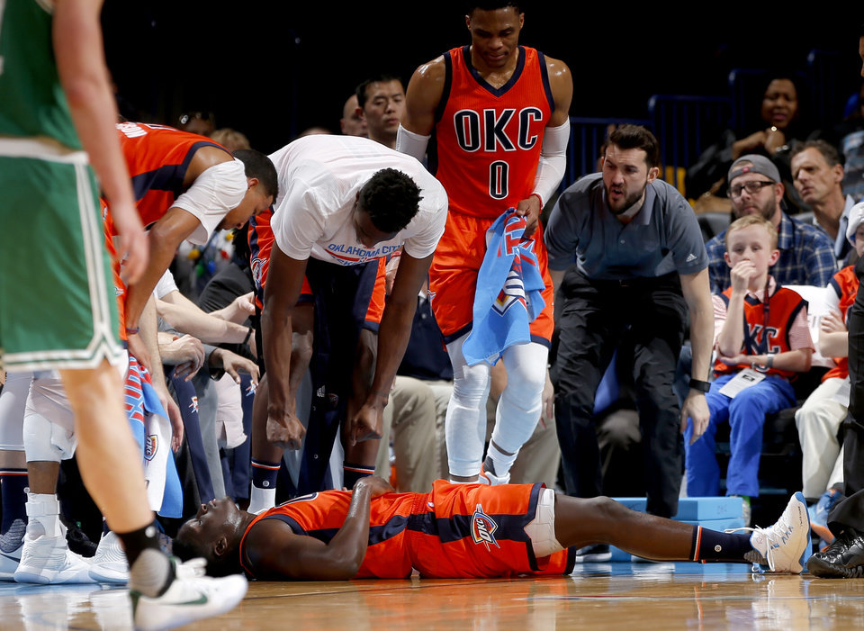 Photo - Victor Oladipo (5) lies on the court after an injury during the NBA game between the Oklahoma City Thunder and the Boston Celtics at the Chesapeake Energy Arena, Sunday, Dec. 11, 2016. Photo by Sarah Phipps, The Oklahoman