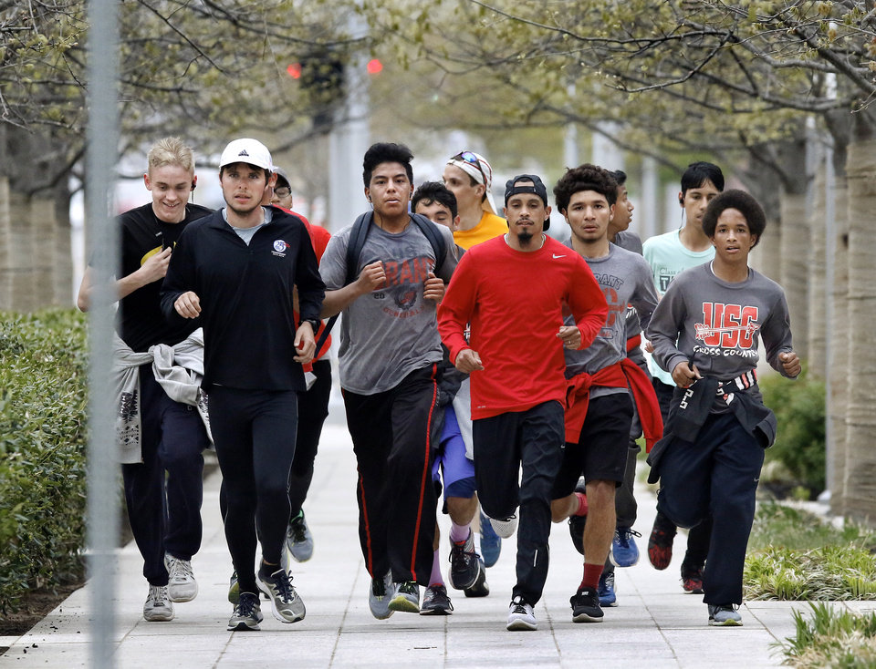 Photo -  Students and others from U.S. Grant High School run east along Sheridan Avenue in front of Myriad Gardens on Friday on their way to the Capitol to show support for teachers on Day 5 of a statewide walkout. [Photo by Jim Beckel, The Oklahoman]