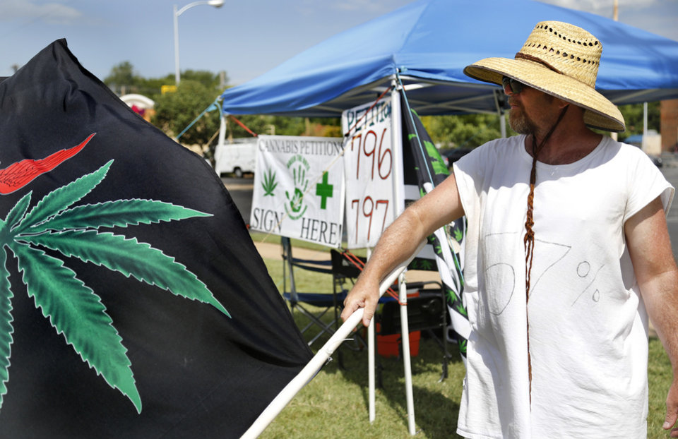 "Photo - A volunteer waves a medical marijuana flag Tuesday morning, Aug. 7, 2018, hoping to attract attention of passing motorists, and convince  them to sign  petitions requesting Oklahomans be given a chance to vote on the issue of recreational marijuana. The man was collecting signatures for SQ 796 and SQ 797 at this tent on Lindsey Street in Norman. He has been there for four days, he said.  He remained optimistic  about gathering signatures on the petitions, saying he ""would like to get 300 today."" He said he's received a lot of positive reaction as drivers pass the tent. Photo by Jim Beckel, The Oklahoman"
