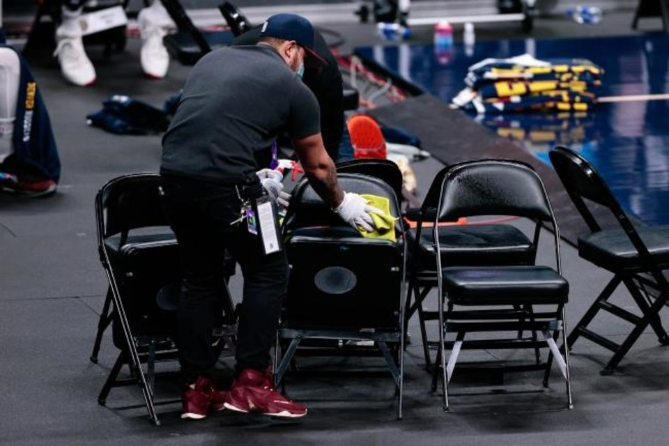 Photo -  A court attendant sanitizes chairs after a timeout during Tuesday's Thunder-Nuggets game in Denver. [Isaiah J. Downing/USA TODAY Sports]