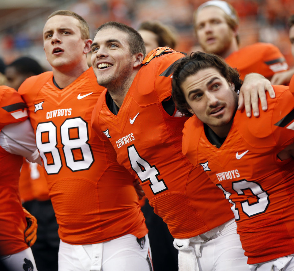 Photo - From left, OSU's Austin Hays, J.W. Walsh and David Glidden sing the alma mater after a college football game between the Oklahoma State University Cowboys (OSU) and the Kansas Jayhawks (KU) at Boone Pickens Stadium in Stillwater, Okla., Saturday, Oct. 24, 2015. OSU won 58-10. Photo by Nate Billings, The Oklahoman