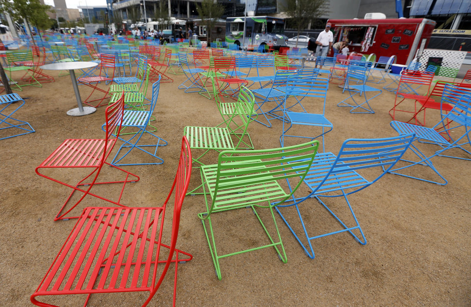 Photo - Colorful chairs near food trucks parked along S. Robinson Ave. during the grand opening weekend of Scissortail Park in Oklahoma City, Saturday, Sept. 28, 2019. [Nate Billings/The Oklahoman]