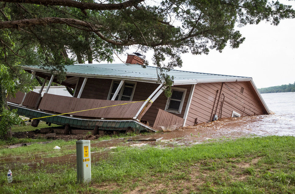 Photo - Flood waters from the Cimarron River wash away a home in the Twin Lakes community near Cimarron City, Okla. on Wednesday, May 22, 2019.  [Chris Landsberger/The Oklahoman]