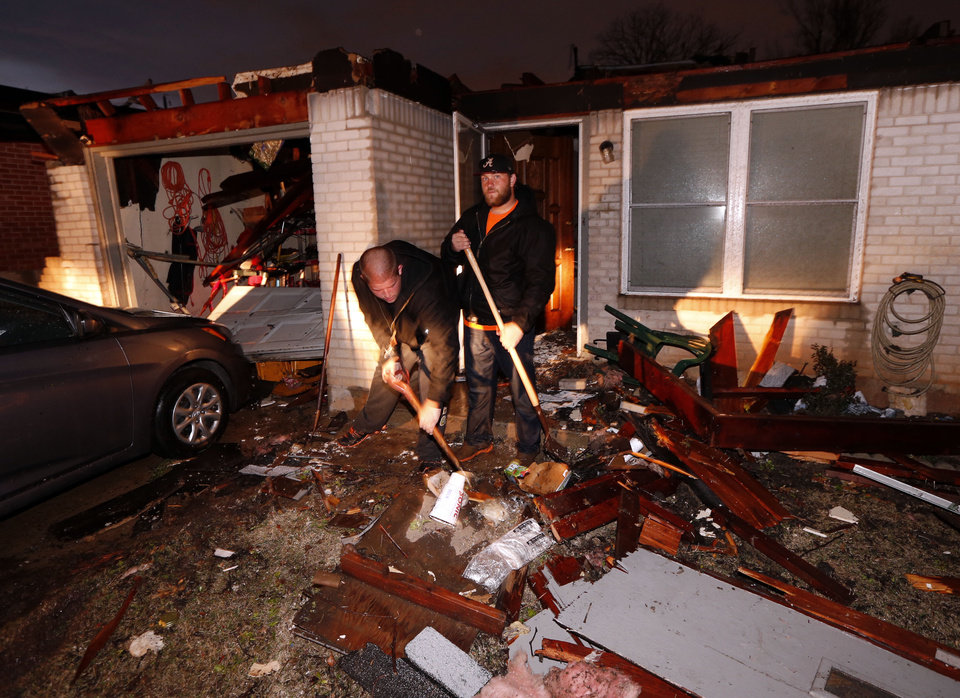 Photo - Chris Howse and Cody Dodge help clean debris from a friends house after tornado force winds blew roofs off houses on Main Street near Janeway on Wednesday, March 25, 2015 in Moore, Okla. Photo by Steve Sisney, The Oklahoman
