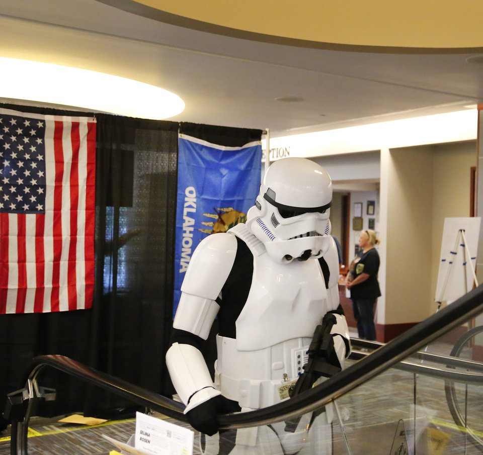 Photo - Wearing a Star Wars stormtrooper costume, this SoonerCon visitor uses a lobby escalator to access the second floor of the Reed Conference Center, 5750 Will Rogers Rd., in Midwest City.  Exhibitor hall is open 10 am - 6p.m. Saturday and 10 a.m -4 p.m Sunday.  Photo by Jim Beckel, The Oklahoman