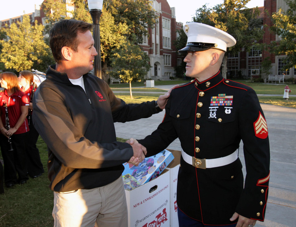Photo - OU / TEXAS / COLLEGE FOOTBALL GAME / ROTC RUN: University of Oklahoma head football coach Bob Stoops shakes hands with Sgt Aaron Smith, OU student, after the OU Naval ROTC began its annual relay run to Dallas on Wednesday, Sept. 29, 2010, in Norman, Okla.  Photo by Steve Sisney, The Oklahoman ORG XMIT: KOD