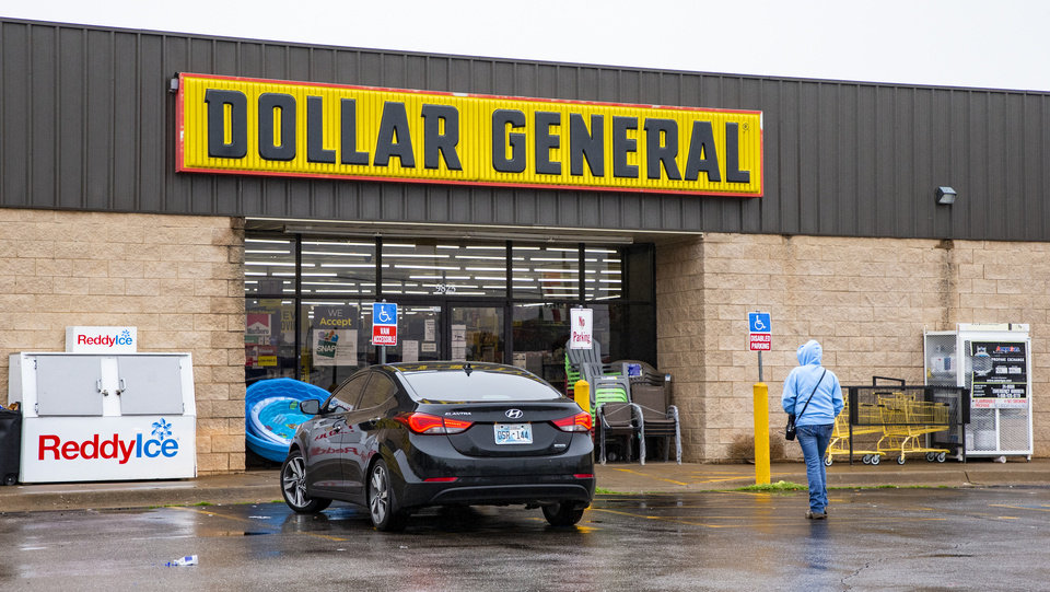 Photo - The exterior of a Dollar General as customer walks into the store in Oklahoma City, Okla. on Tuesday, March 17, 2020.  [Chris Landsberger/The Oklahoman]